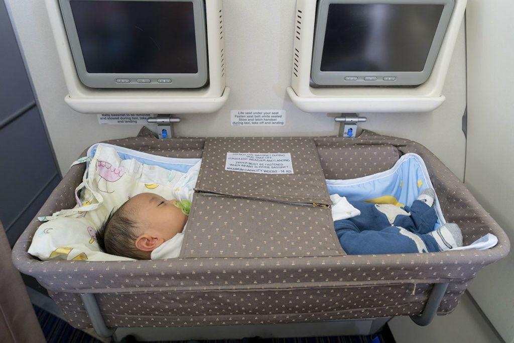 Ein kleines Baby schläft in einem Bassinet, einer Art Körbchenbett das im Flugzeug vor den Sitzen der Eltern festgemacht werden kann.