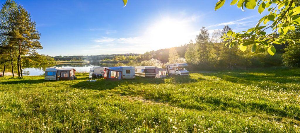 Sommer, das Gras ist saftig grün, die Sonne strahlt bereits. An dem ruhigen See haben fünf Wohnwagen ihr Lager aufgeschlagen.