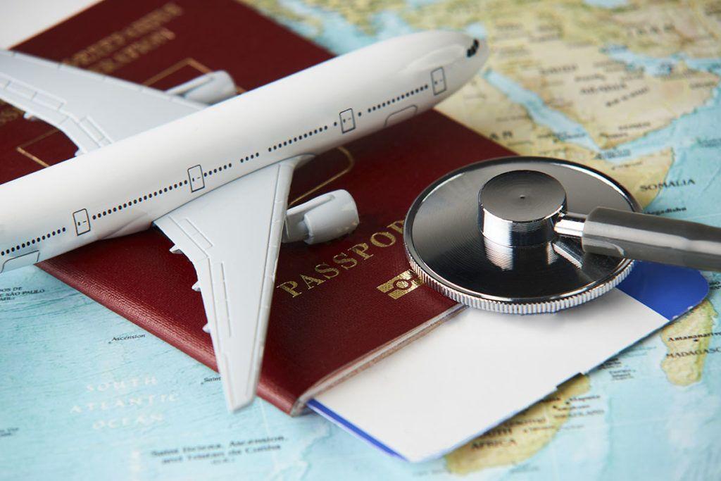 Auf einer Landkarte liegt ein Reisepass mit einem Flugticket, ein Stethoskop und ein Spielzeugflugzeug.