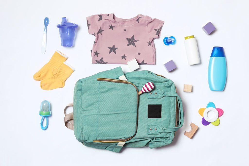 Ein blauer Rucksack liegt auf dem Boden, drumherum verteilt sind Babyklamotten, Spielsachen und wichtige Utensilien wie Ersatzschnuller und Babypuder