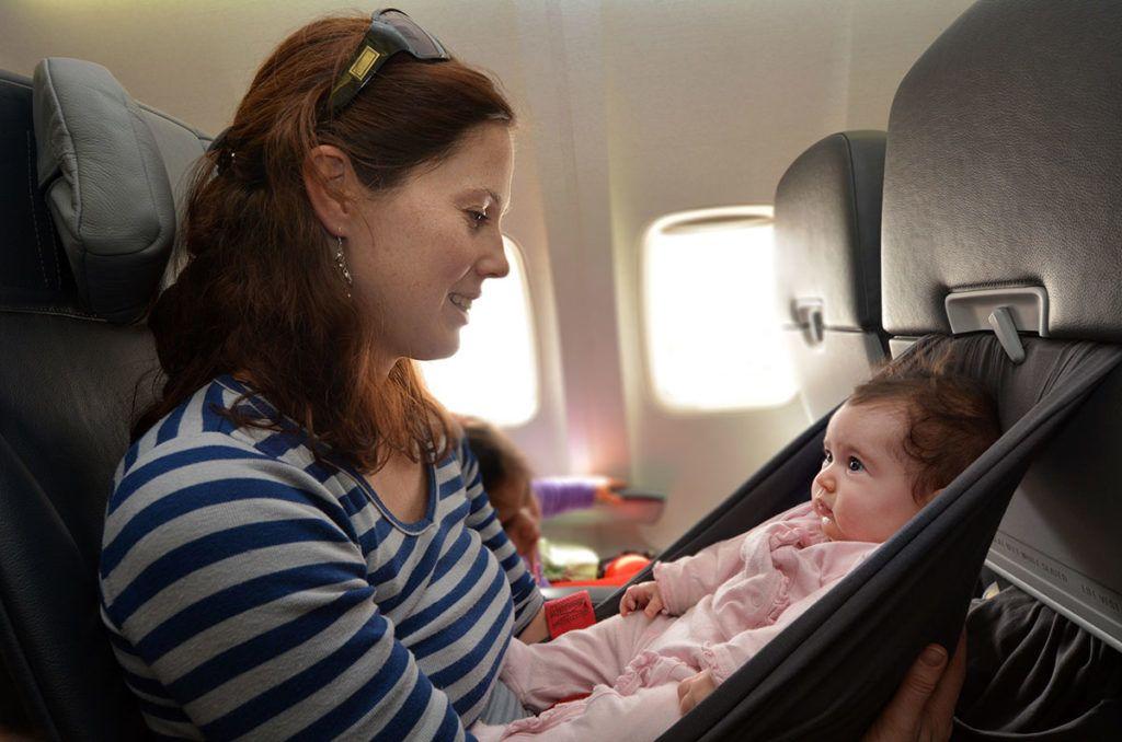 Im Flugzeug: ein Säugling sitzt auf einem Tuch das in dem Vordersitz eingeklemmt ist und schaut seine Mutter skeptisch an.