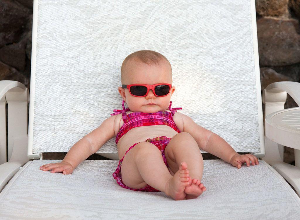 Ein Baby mit roter Sonnenbrille und pink kariertem Bikini liegt entspannt auf einer Sonnenliege.