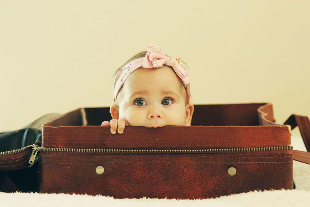 Ein kleines Baby mit Schleifchen auf dem Kopf liegt in einem braunen Koffer und schaut über den Rand und knabbert dabei am Koffer.