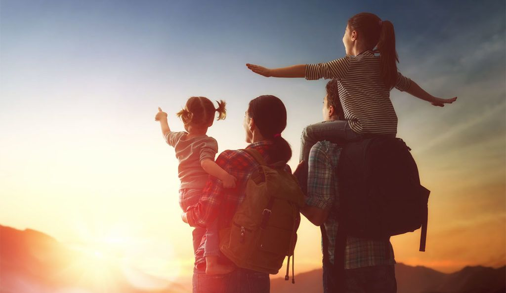 Eine junge Familie blickt Richtung Horizont, der Vater trägt eine ältere Tochter auf den Schultern. Sie streckt die Arme aus wie ein Flugzeug. Die Mutter trägt ein jüngeres Machen auf dem Arm, die Richtung Sonne zeigt.