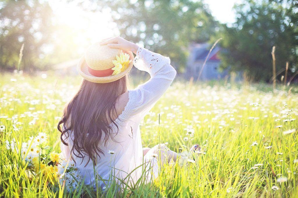 Eine grüne große Lichtung, im Hintergrund ist verschwommen ein blaues Holzhaus, eine Frau sitzt mit dem Rücken zu uns. Sie hat lange, gewellte, schwarze Haare, hält ihren Hut mit der Hand fest und schaut über die Lichtung
