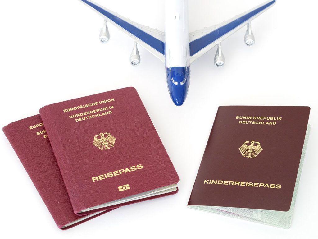 Drei Reisepässe liegen auf weißem Untergrund, einer davon ist ein Kinderreisepass. Dahinter steht ein blau-weißes Spielzeugflugzeug.