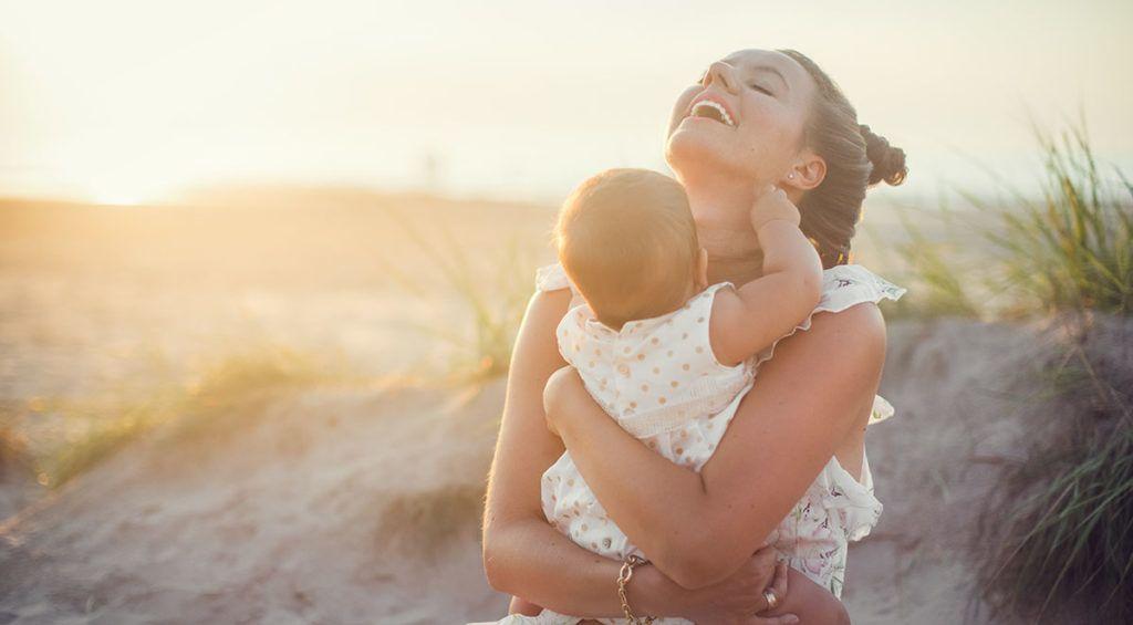 Eine Mutter sitzt mit ihrem Baby auf dem Arm im Sand, das Baby zwickt ihr in den Hals, sie lacht.