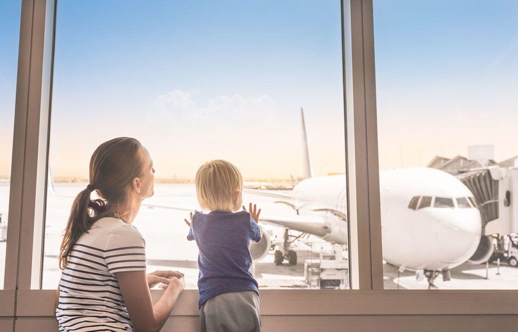 Am Flughafenterminal: Ein Kind steht an der Scheibe und schaut auf das Flugzeug. Die Mutter sitzt entspannt daneben.