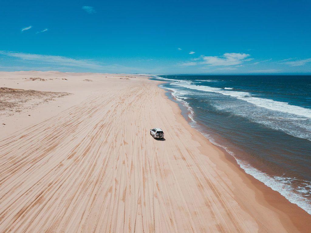 Ein weißes Auto fährt über einen riesigen menschenleeren Strand.