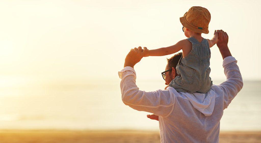 Ein kleines Kind sitzt auf den Schultern seines Vaters. Beide blicken auf das Meer Richtung Sonnenuntergang.
