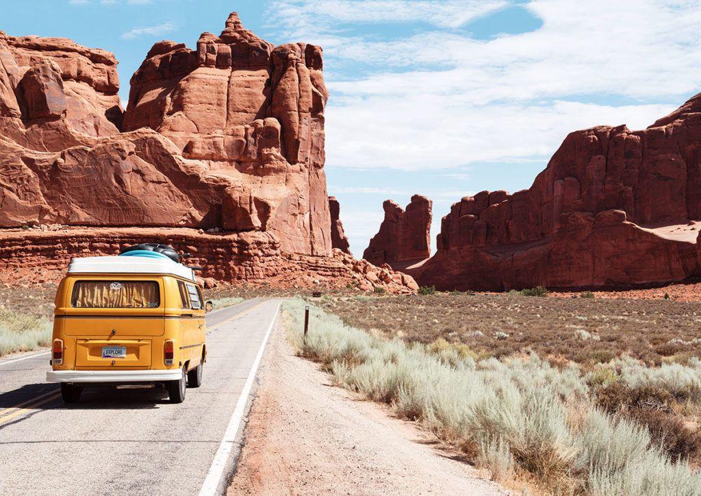 Ein gelber Campingbus fährt über eine trockene Landstraße auf die rotbraunen Berge der Grand Canyon zu.