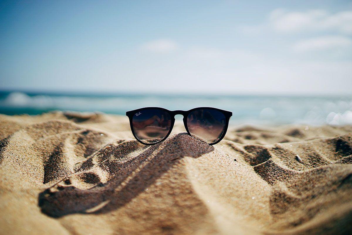 Eine schwarze Sonnenbrille liegt auf einem kleinen Sandhaufen am Strand. Im Hintergrund glitzert das Meer.