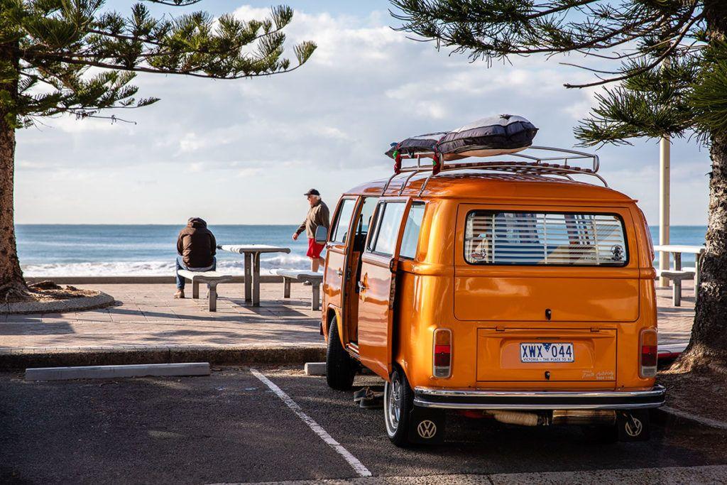 Ein gelber Bulli steht mit offenen Türen auf einem schattigen Parkplatz am Meer. Auf einer Bank sitzt ein Mann, weiter vorne spaziert ein älterer Mann über die Promenade.